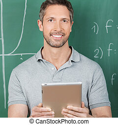 Male Teacher Holding Digital Tablet Against Chalkboard