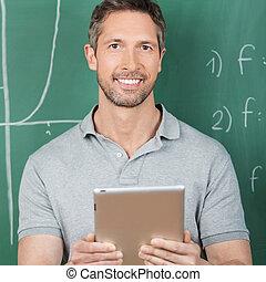 Male Teacher Holding Digital Tablet Against Chalkboard