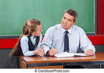 Male Teacher Looking At Schoolgirl In Classroom