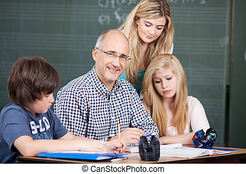 Male teacher surrounded by his pupils