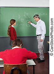 Male Teacher Teaching Geometry To Girl In Classroom