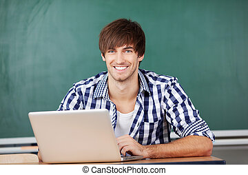 Male Teacher With Laptop Sitting At Desk Against Chalkboard