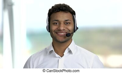 Male technical support operator in headset. Customer service worker talking to camera on blurred background. Call center operator at work.
