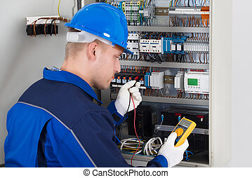 Male Technician Examining Fusebox With Digital Insulation...