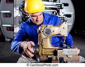 technician fixing industrial sewing machine