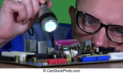 Male technician guy with glasses inspecting computer...