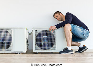 Male technician installing air-conditioning system.