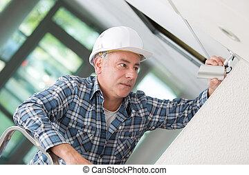 male technician installing camera on wall