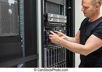 Male Technician Installing Hard Drive In Datacenter
