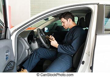 Male Technician Preparing Checklist In Car At Repair Shop
