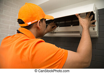 Male technician repairing air conditioner on the wall