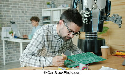 Male technician is busy repairing microcircuit board with solderer making robot, young woman is using computer in background. People and work concept.