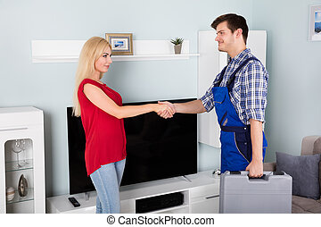 Male Technician Shaking Hand With Woman