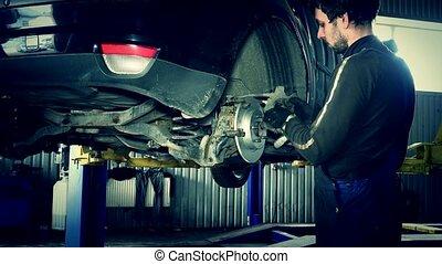 male technician working on customer car brake system.
