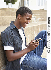 Male Teenage Student Sitting Outside On College Steps Using Mobile Phone