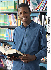 Male Teenage Student Studying In Library