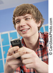 Male Teenage Student Using Mobile Phone By Lockers In School