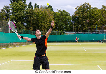 Male tennis player are serving on a court