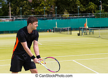 Male tennis player getting ready to serve on a court outdoor