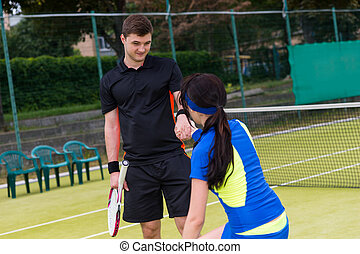 Male tennis player helps his female partner to stand up