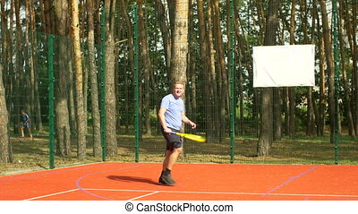 Male tennis player hitting backhand in tennis game