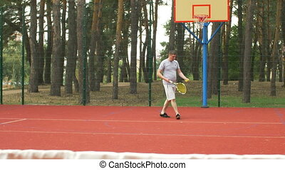Male tennis player hitting serve on outdoor court