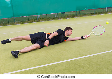 Male tennis player in action during the game fallen on a court