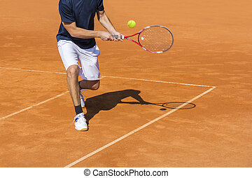 Male tennis player in action on the clay court on a sunny day