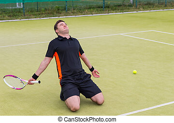 Male tennis player is sitting on his knees because of the loss in tennis match