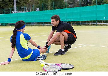 Male tennis player massaging woman's injured leg after match