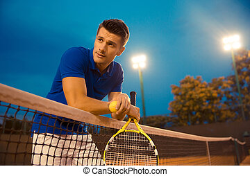 Male tennis player standing in the court