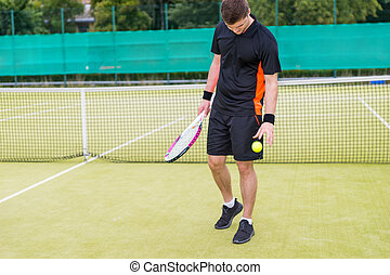 Male tennis player throws the ball after a match at tennis court