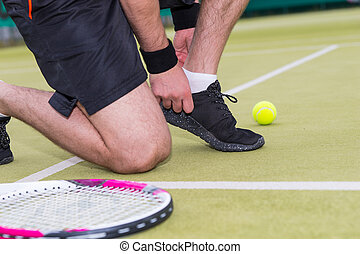 Male tennis player tying shoelaces left racket and ball on a court