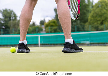 Male tennis player's legs during the game on green grass court outdoors