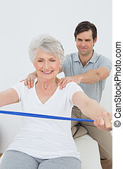 Male therapist assisting senior woman with exercises in the...