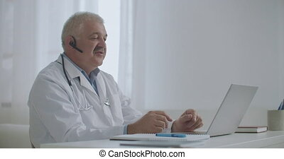 male therapist is sitting in his office of medical clinic and talking online by videochat with patients or colleagues