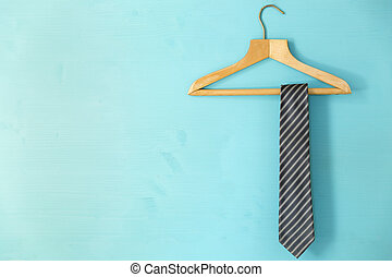 Male tie hanging on the rack, blue background. Father's day concept