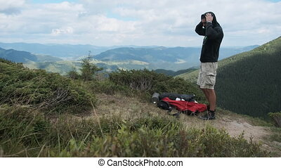 Male Tourist Changes Clothes While Standing on a Mountain Hill with a Backpack. Landscape view of mountain range, clouds. Hiking, hike. Mountain tourism, Mountain climbing process. Timelapse.