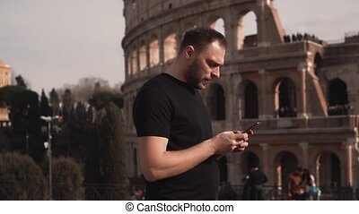 Male tourist in Rome, Italy serving the internet, writing emails, watching photos. Man walks on Colosseum. Slow motion.