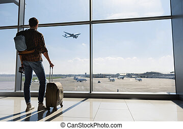 Male tourist looking at flight - Young man is standing near ...
