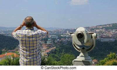 Male tourist looking through binoculars