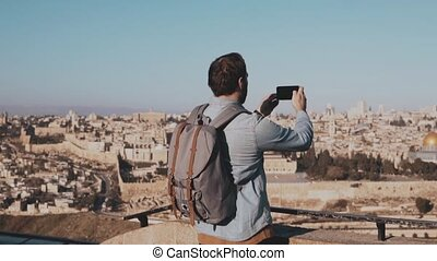 Male tourist takes smartphone photos of Jerusalem. European...