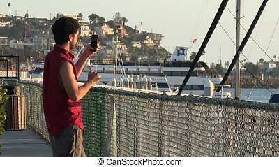 Male tourist taking pictures of the marina - Handsome young...