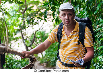 male tourist with a backpack in the jungle resting