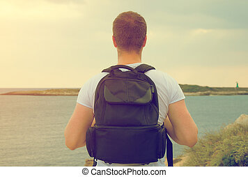 Male tourist with backpack looking at the ocean.