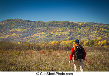 Male tourist with backpack sotret on the horizon in autumn