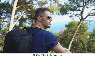 Male tourist with big rucksack on the hill.