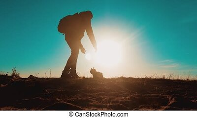 Male tourist with dog stands on top man of a mountain....