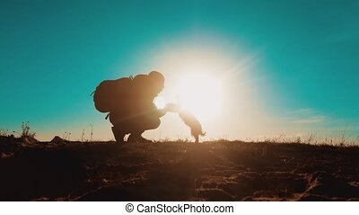 Male tourist with dog stands on top man of a mountain. smartphone navigation man silhouette at sunset. hikers adventure and the dog go walking. travel mountains silhouette friendship and lifestyle love