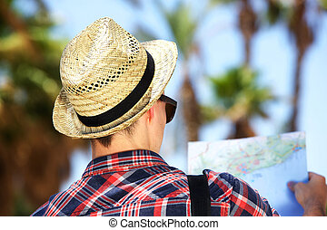 Male tourist with hat looking at map on vacation